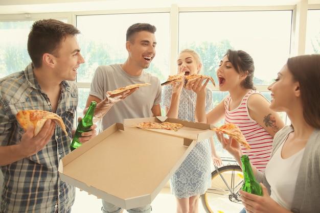 Junge leute, die spaß an der party mit köstlicher pizza drinnen haben