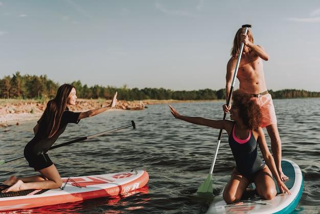 Junge leute, die surfs im meer mit paddeln rudern
