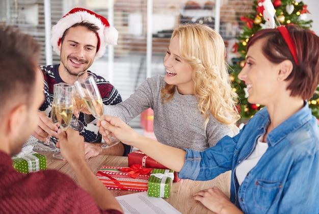 Junge leute, die während der weihnachtsfeier anstoßen