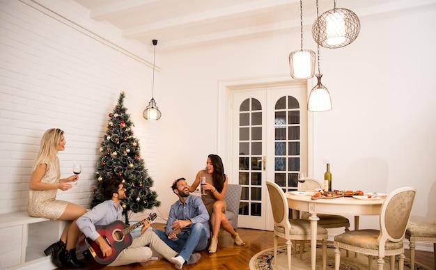 Junge leute, die zu hause weihnachten und neues jahr durch tannenbaum feiern