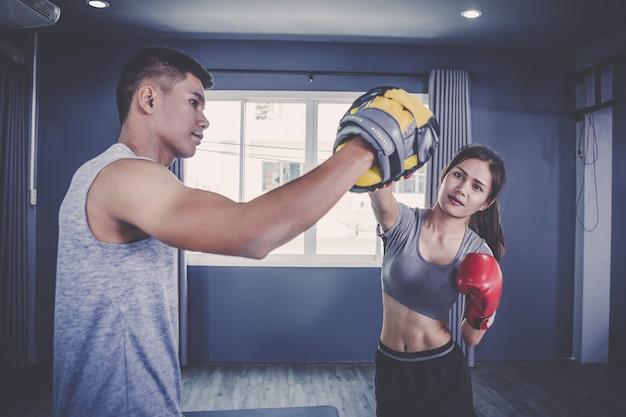 Junge leute, die zum boxen und zur beinarbeit in der trainingsklasse üben