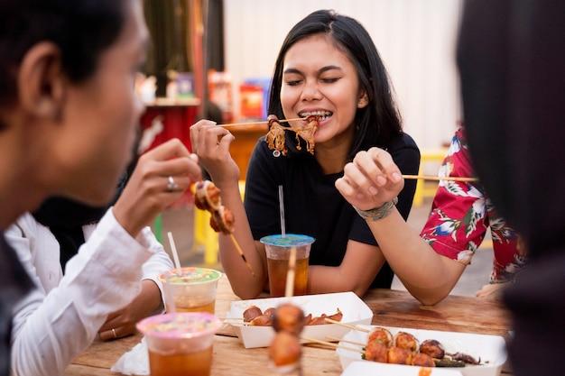 Junge leute essen zusammen auf dem außenplatz zu mittag