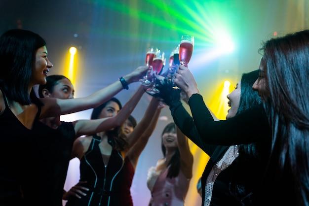 Junge leute feiern eine party, trinken und tanzen