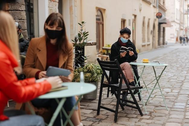 Junge leute, gekleidet in lässiger warmer kleidung, die auf caféterrasse auf distanz sitzt und medizinische schutzmasken trägt. pandemie maßnahmen konzept.
