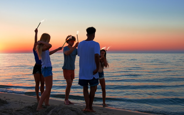 Junge leute haben spaß am strand mit funkelnden kerzen in den händen