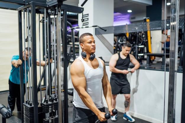 Junge leute im fitnessstudio trainieren gewichte.