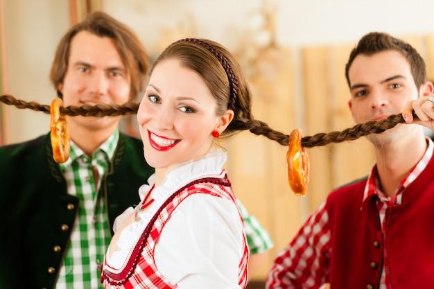 Junge leute im traditionellen bayerischen tracht im restaurant oder in der kneipe