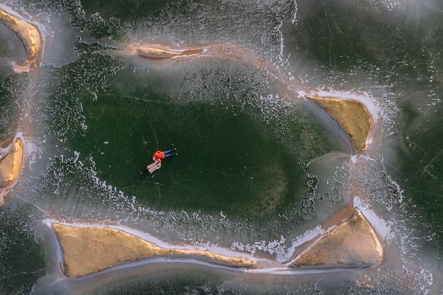 Junge leute in daunenjacken liegen auf dem eis gefrorener sandgruben. der blick von oben