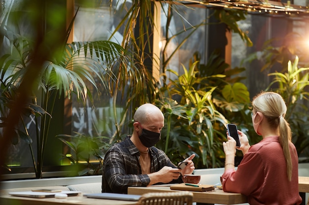 Junge leute in schutzmasken, die online am handy arbeiten, das im café sitzt