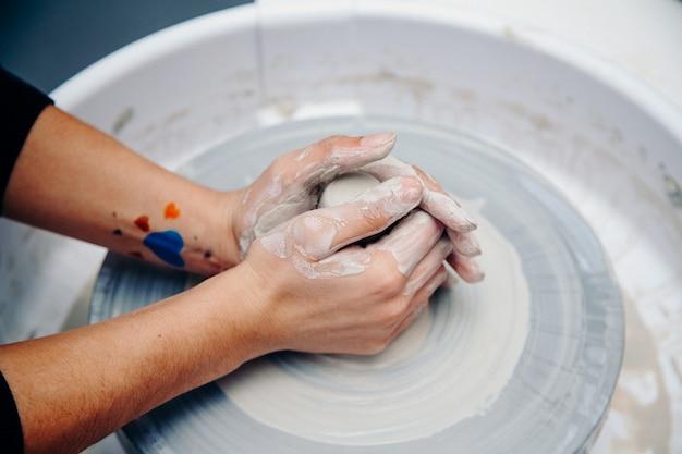 Junge leute lernen handwerkliche keramik auf der töpferscheibe