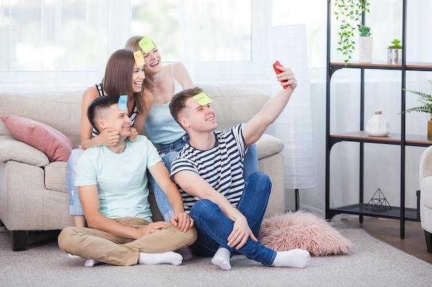 Junge leute machen drinnen selfie. gruppe von freunden, die einen schuss auf dem smartphone machen. menschen, die sich selbst ein bild machen.