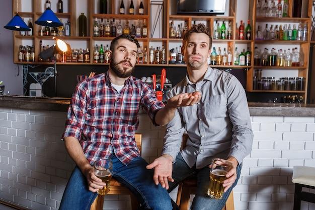 Junge leute mit aufpassendem fußball des bieres in einer bar