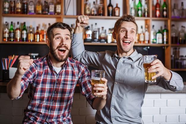 Junge leute mit bier, die fußball in einer bar schauen