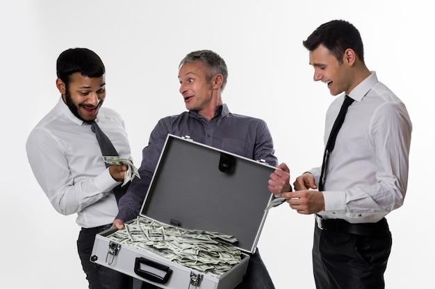Junge leute mit einem koffer voller geld erfolgreiche leute