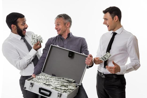 Junge leute mit einem koffer voller geld geschäftsleute haben viel geld verdient