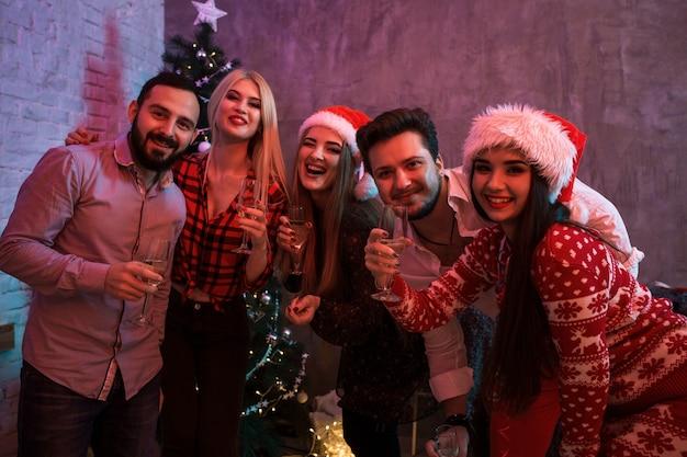 Junge leute mit gläsern champagner auf weihnachtsfeier Premium Fotos