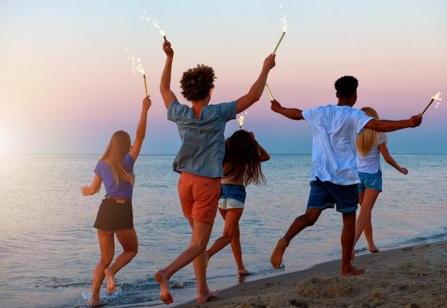 Junge leute rennen mit funkelnden kerzen in den händen am strand
