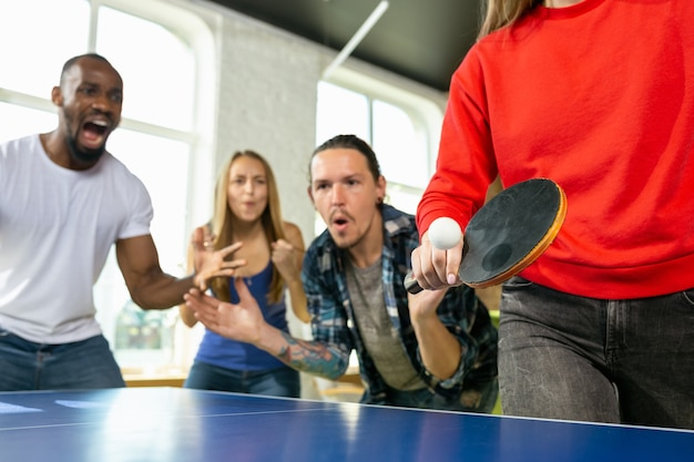 Junge leute spielen tischtennis am arbeitsplatz und haben spaß. freunde in freizeitkleidung spielen am sonnigen tag zusammen tischtennis. konzept der freizeitaktivität, sport, freundschaft, teambuilding, teamwork.