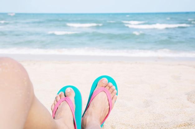 Junge leute tragen die schuhe sandalen nahaufnahme füße schlafen entspannend am strand auf sand genießen kühle sonne an sonnigen sommertag. das meer / meer genießen. der fokus liegt auf den füßen