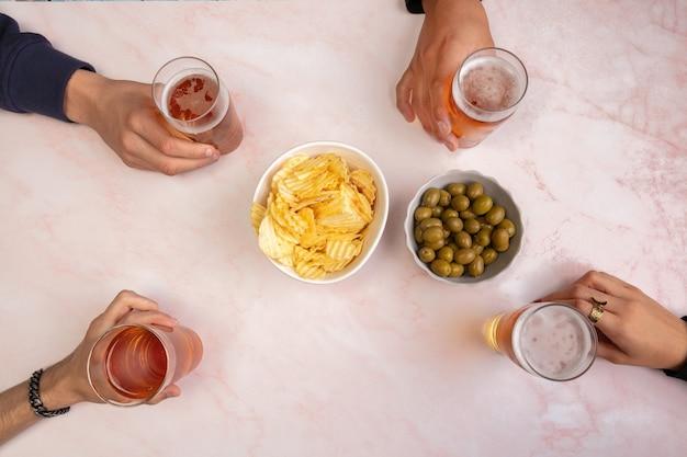 Junge leute trinken bier und haben eine gute zeit auf einem tisch