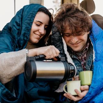 Junge leute trinken kaffee aus ihrem van