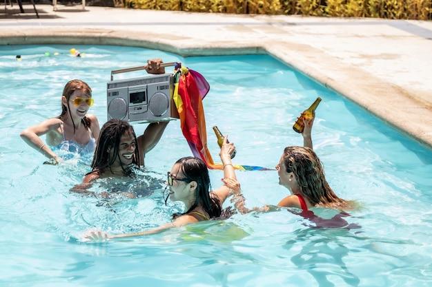 Junge leute verschiedener ethnien, die partybier in einem schwimmbad trinken