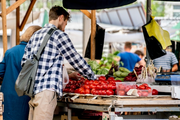 Junge leute wählen frisches reifes gemüse auf dem freiluftmarkt und kaufen es