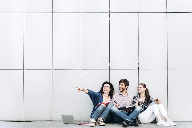 Junge leute zeigen sich auf einem freien platz für text, lächelnd und sitzen in der nähe der wand. studenten studieren. bildung social media konzept.