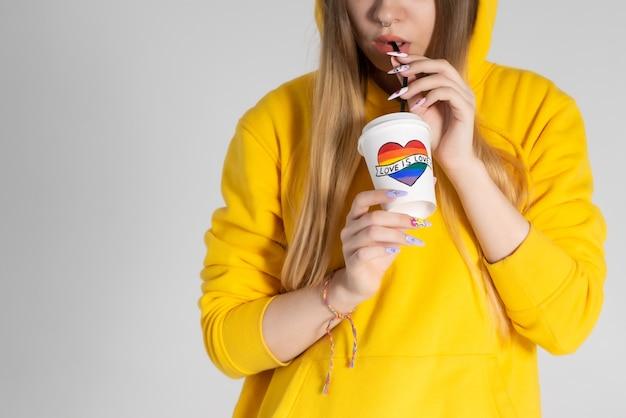 Junge lgbtq-frau, die gelbe kapuzenjacke trägt, die kaffee von einer tasse mit regenbogenherz trinkt.