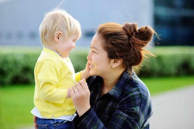 Junge liebende asiatische frauen mit nettem kaukasischem kleinkindjungen.