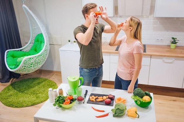 Junge liebende familie hat spaß mit bio-tomaten und chili-pfeffer beim kochen von gemüse in der weißen küche.