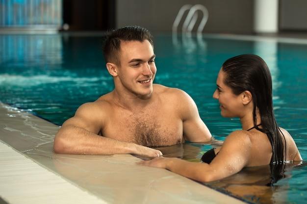 Junge liebende paare, die sich zusammen im badekurortpool entspannen