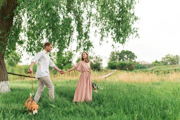 Junge liebespaare, die spaß haben und auf dem grünen gras auf dem rasen mit ihrem geliebten inländischen hunderasse spürhund und einem blumenstrauß von wildblumen laufen