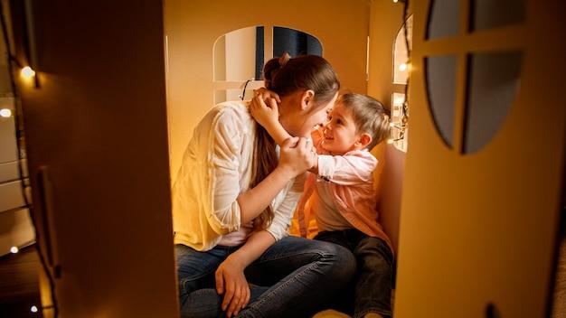 Junge liebevolle mutter, die sich nachts mit ihrem kleinen sohn im zelt- oder kartonspielzeughaus umarmt. konzept von kinderliebenden eltern und familie, die nachts zeit zusammen haben.