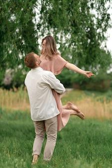 Junge liebevolle paare, die auf das grüne gras auf dem rasen umarmen und tanzen. schöne und glückliche frau und mann berühren sich leicht. schönes paar verliebt. mädchen im kleid und der mann im hemd