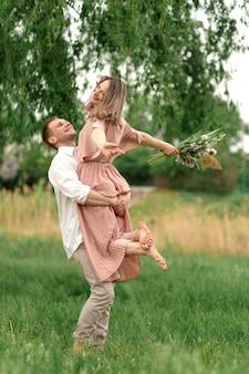 Junge liebevolle paare, die auf das grüne gras auf dem rasen umarmen und tanzen