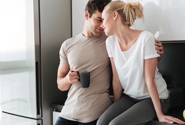 Junge liebhaber, die das umarmen bei der stellung in der küche genießen