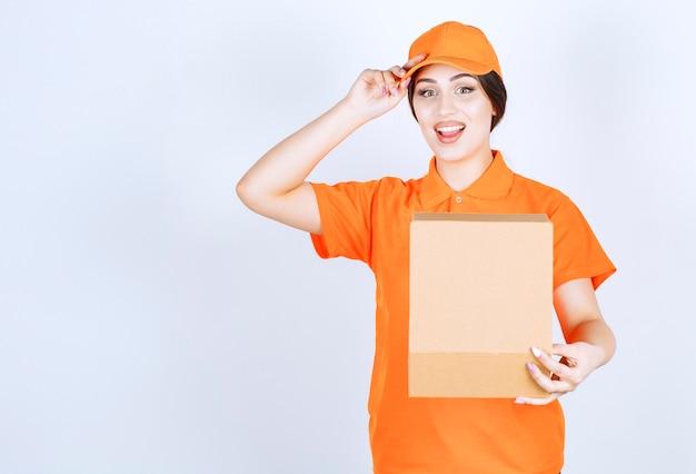 Junge lieferfrau auf weißer wand in orangefarbenem unishape