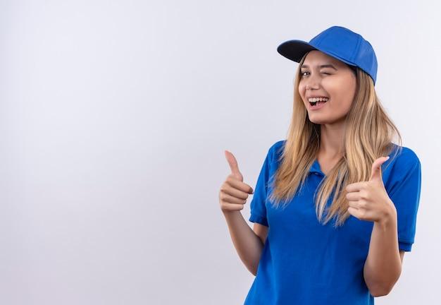 Junge lieferfrau blinkt, trägt blaue uniform und verschließt ihren daumen