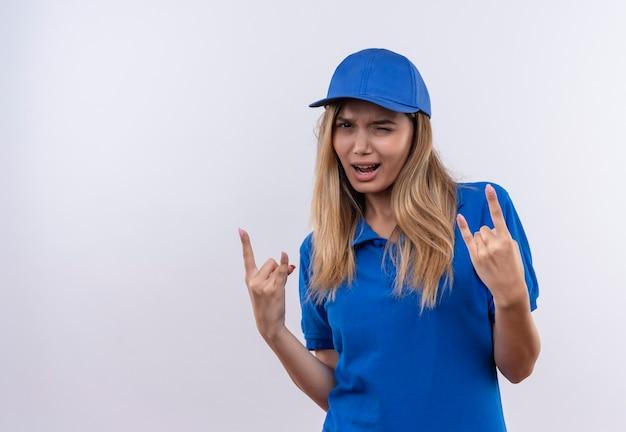 Junge lieferfrau, die blaue uniform und mütze zeigt, die ziegengeste zeigt