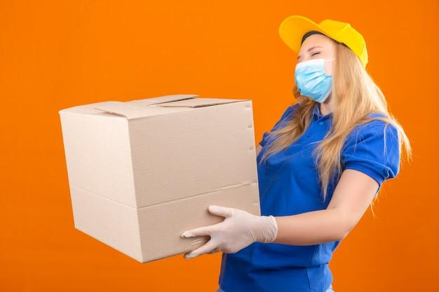 Junge lieferfrau, die blaues poloshirt und gelbe kappe in der medizinischen schutzmaske trägt, die mit pappkarton steht, der fröhlich über lokalisierten dunkelgelben hintergrund lächelt