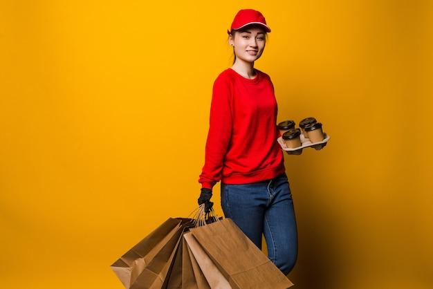 Junge lieferfrau, die kaffee und papiertüten lokalisiert auf gelber wand hält