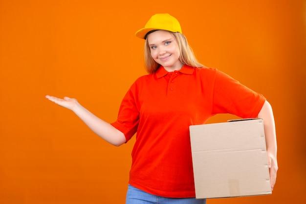 Junge lieferfrau, die rotes poloshirt und gelbe kappe trägt, die fröhlich präsentiert und mit handfläche betrachtet, die die kamera über lokalisiertem orangefarbenem hintergrund betrachtet