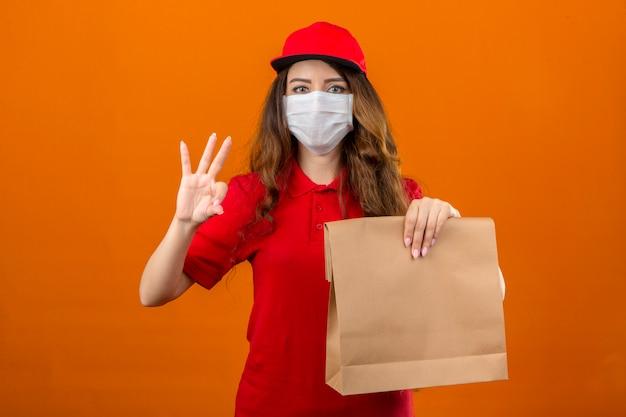 Junge lieferfrau, die rotes poloshirt und kappe in der medizinischen schutzmaske trägt, die mit papierverpackung zeigt und oben mit den fingern nummer drei zeigt, während über isoliertes orange lächelt