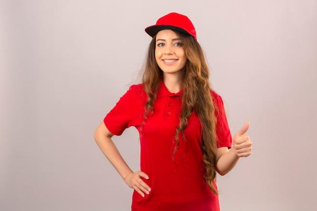 Junge lieferfrau, die rotes poloshirt und kappe lächelnd zuversichtlich zeigt daumen oben über lokalisiertem weißem hintergrund