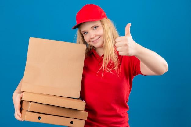 Junge lieferfrau, die rotes poloshirt und kappe trägt, die mit pizzaschachteln und papierpaket zeigt, zeigt daumen oben lächelnd freundlich über lokalisiertem blauem hintergrund