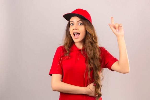 Junge lieferfrau, die rotes poloshirt und kappe trägt, die überraschtes zeigen des neuen ideenkonzepts des fingers über lokalisiertem weißem hintergrund suchen