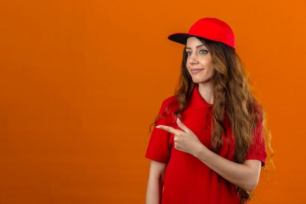 Junge lieferfrau, die rotes poloshirt und kappe trägt, die zur seite zeigen, um kopienraum über lokalisiertem orangefarbenem hintergrund zu präsentieren