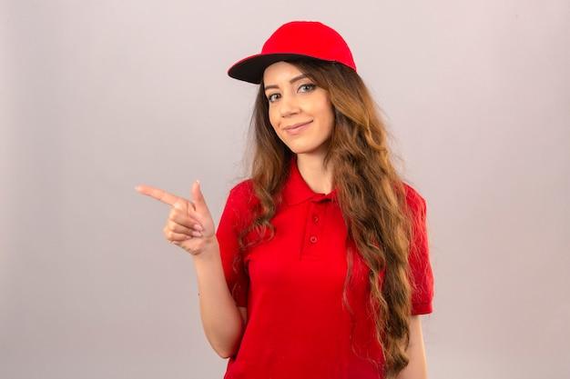 Junge lieferfrau, die rotes poloshirt und kappe trägt, die zuversichtlich zeigt, mit dem finger zur seite über lokalisiertem weißem hintergrund zu zeigen