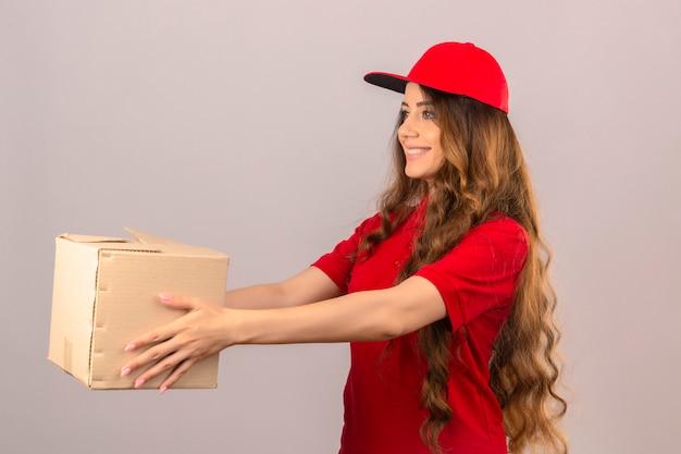 Junge lieferfrau, die rotes poloshirt und kappe trägt junge lieferfrau, die rotes poloshirt und kappe trägt, die dem kunden pappkarton mit lächeln auf gesicht über lokalisiertem weißem hintergrund gibt